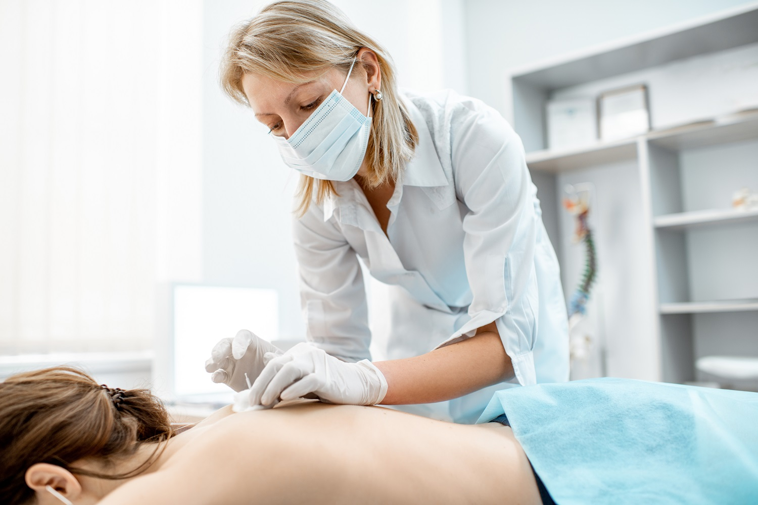 Neuropathologist puts needles into the woman's back removing inflammation of the muscles during the acupuncture treatment in the office