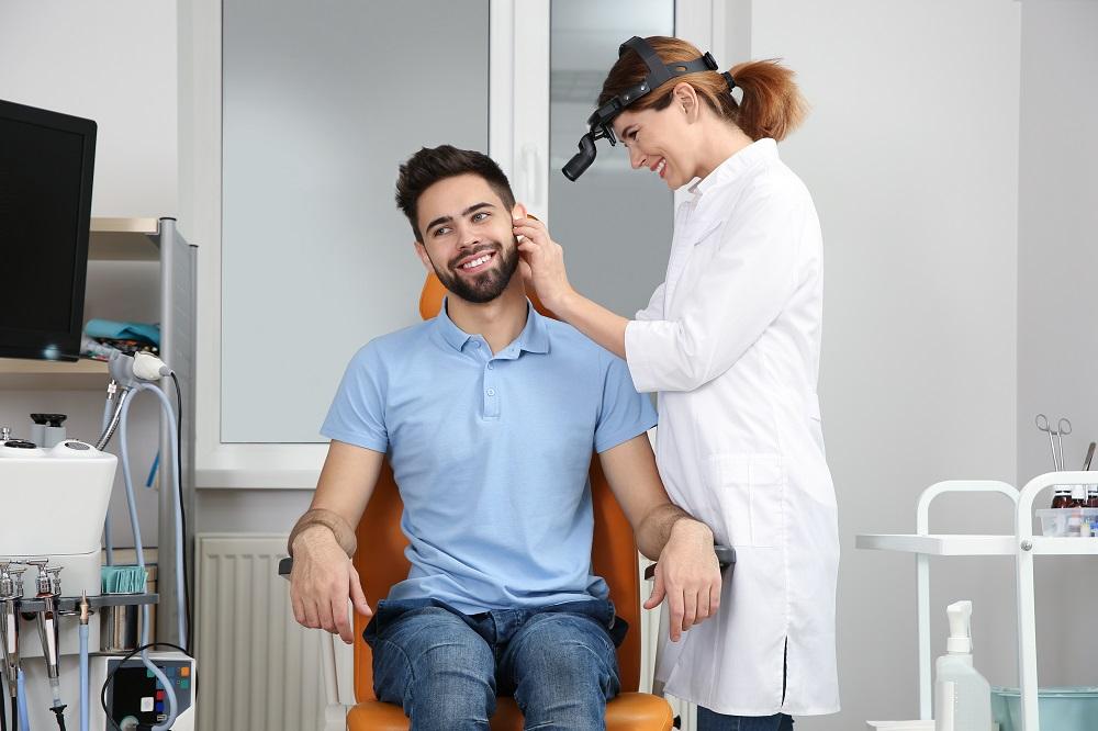 Professional otolaryngologist examining man in clinic. Hearing disorder