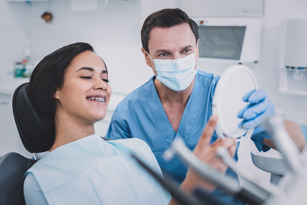 So cute. Pleased dentist wearing uniform while consulting his visitor