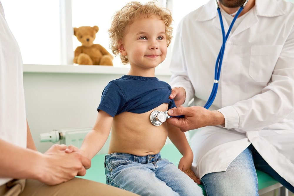 Portrait of adorable little boy visiting doctor, looking brave and smiling, holding mothers hand while pediatrician listening to heartbeat with stethoscope