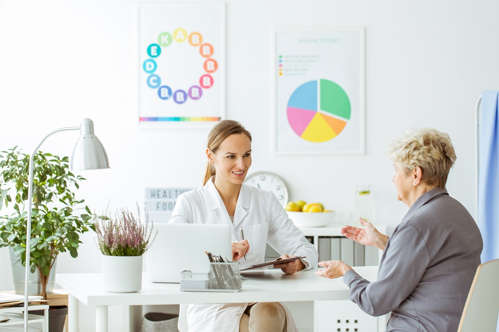 Smiling dietitian in uniform during consultation with a patient in bright office with posters