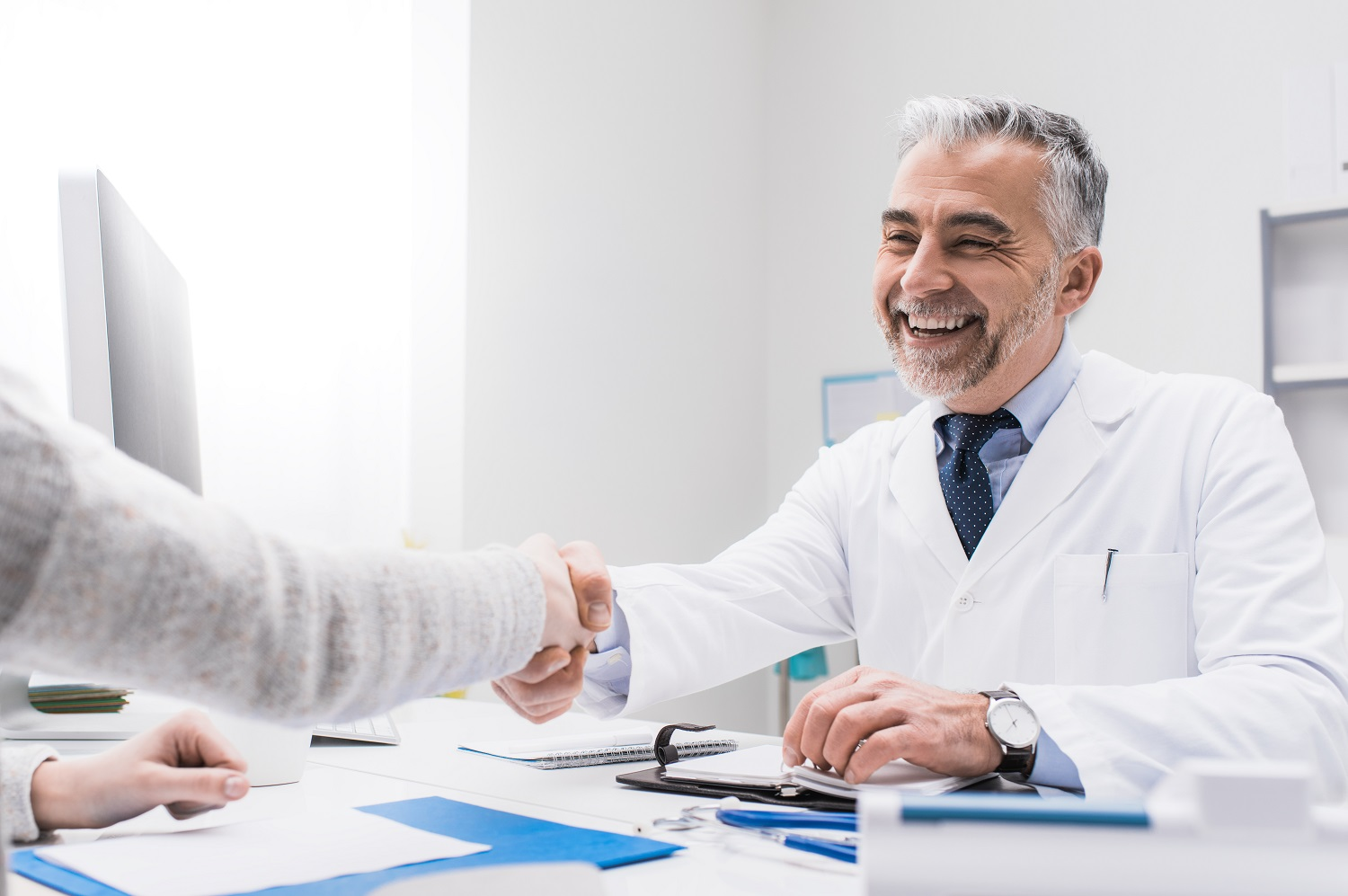 Smiling doctor and female patient shaking hands, healthcare professionals concept