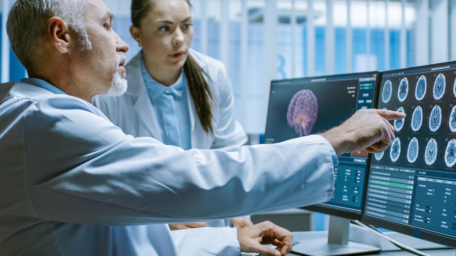 Two Medical Scientists in the Brain Research Laboratory Discussing Progress on the Neurophysiology Project Curing Tumors. Neuroscientists Use Personal Computer with MRI, CT Scans Show Brain Images.