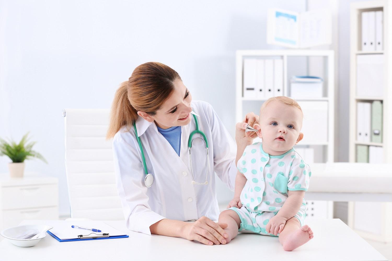 Children's doctor examining baby's ear in hospital